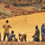 Artisanal miners wash at a rudimentary dam on the site, where excess water is pumped into © Guy Oliver / IRIN